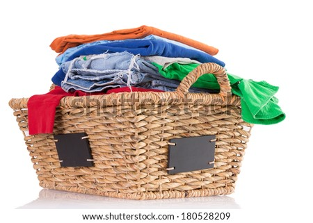 Pile of colorful clean washed fresh clothing in a rustic woven wicker basket with blank labels on the sides ready to be ironed, low angle side view isolated on white - stock photo