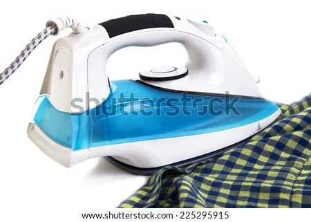 Pile of colorful clothes and electric iron on blue background - stock photo