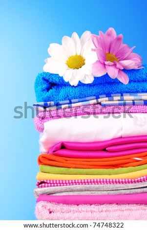 Pile of colorful clothes and flowers   on blue background