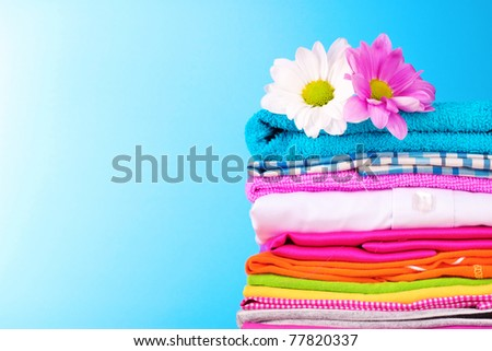 Pile of colorful clothes and flowers   on blue background - stock photo