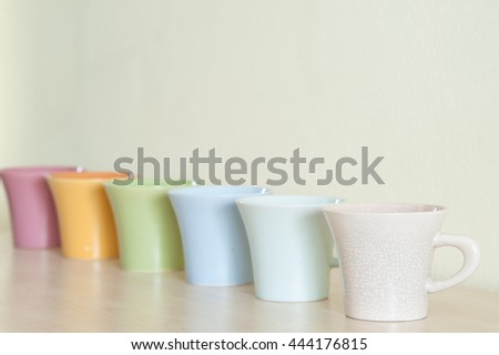 Pile of colorful coffee cups on wooden table with cream background.