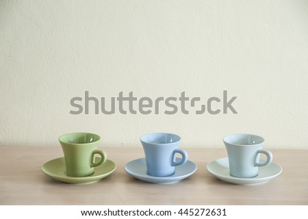 Pile of colorful coffee cups on wooden table with the dishes for prepare serve. - stock photo