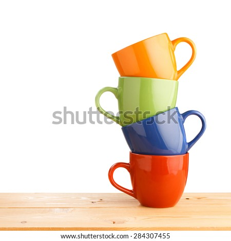 Pile of colorful cups on wooden table isolated on white background - stock photo