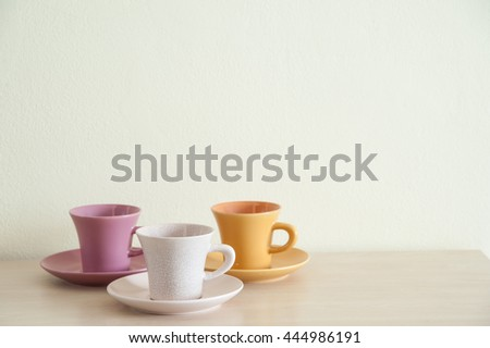 Pile of colorful modern coffee cups on wooden table with dishes for prepare serve. Right space frame.