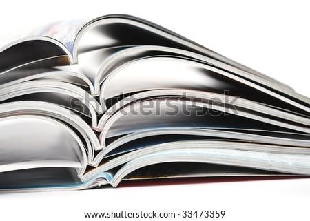 pile of colorful opened magazines on white background - stock photo