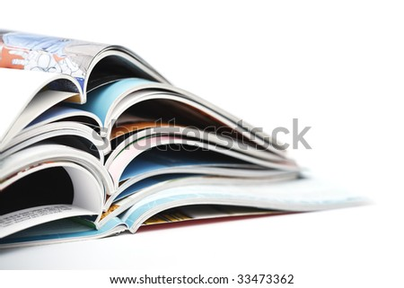 pile of colorful opened magazines on white background - stock photo