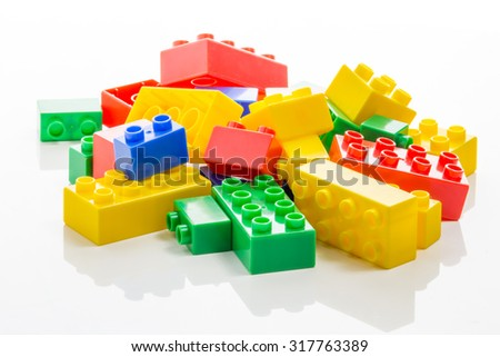 Pile of colorful plastic building bricks on white background - stock photo