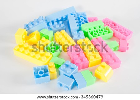 Pile of colorful plastic toy construction bricks isolated over the white as a  background.