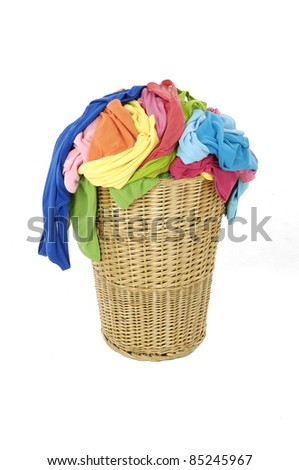 pile of colorful shirts in a wicker basket, isolated