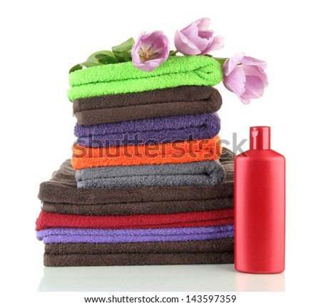 Pile of colorful towels and bottle of conditioner for laundry, isolated on white - stock photo