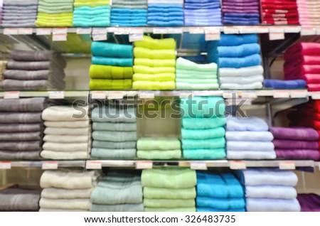 Pile of colorful towels on a shelf in the store, blurred image background