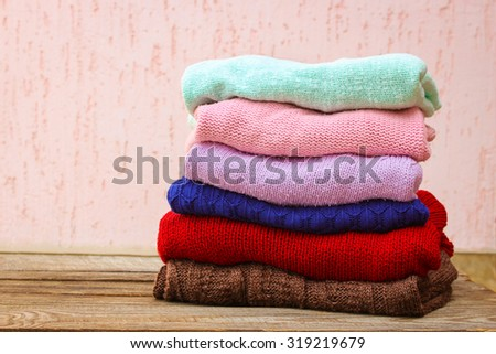 Pile of colorful warm clothes on wooden background. - stock photo