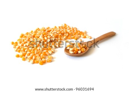Pile of corn grains with a wooden spoon on white background, healthy food concept
