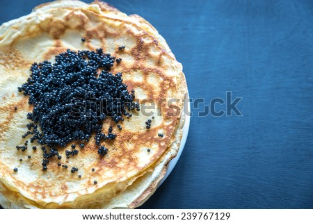 Pile of crepes with black caviar - stock photo