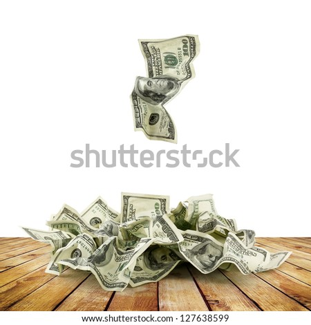 Pile of crumpled money dollar bills on wood planks overs white background - stock photo