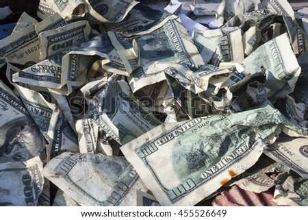 Pile of crumpled one hundred-dollar bills on the ground. - stock photo