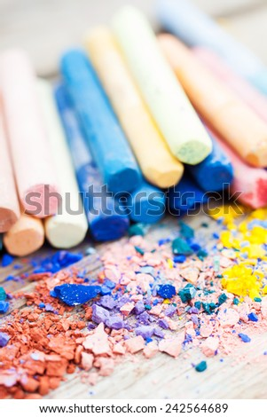 Pile of crushed chalk closeup and rainbow colored pastel crayons on background on wooden desk. Selective focus. - stock photo