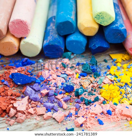 Pile of crushed chalk closeup and rainbow colored pastel crayons on background. Selective focus. - stock photo