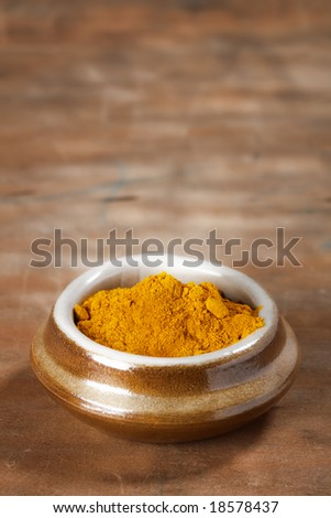 pile of Curry powder in a pot on old wooden background, shallow DOF - stock photo