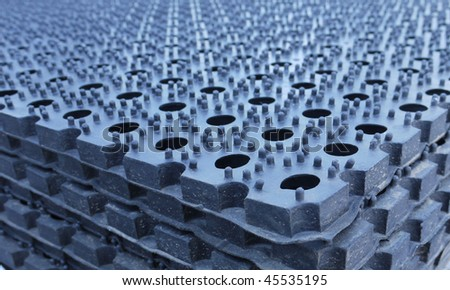 Pile of dark-grey rubber rugs with round black holes - stock photo