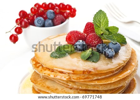 Pile of delicious handmade pancakes topped with honey, raspberries and bilberries on feast table - stock photo