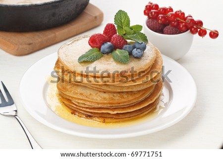 Pile of delicious handmade pancakes topped with raspberries and bilberries on feast table - stock photo