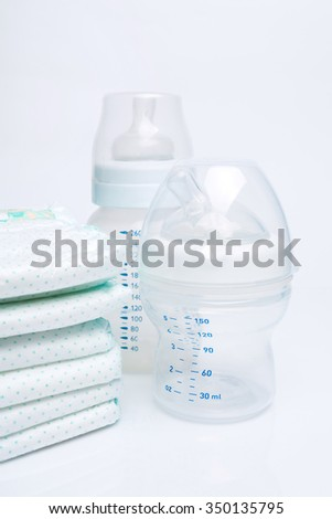 Pile of diapers and baby bottles isolated on white background - stock photo