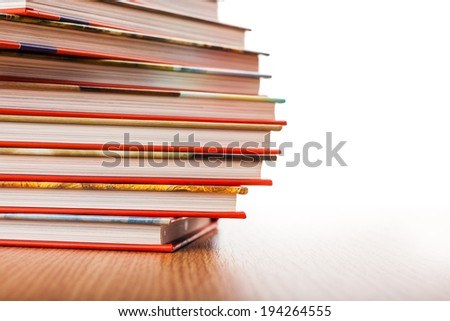 Pile of different books put on a wooden table