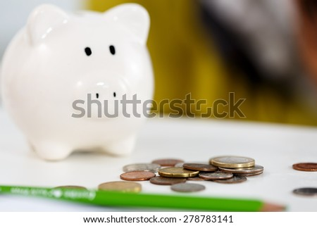 Pile of different coins near white piggybank on table closeup. Budgeting expenses concept. Making savings and effective investment concept
