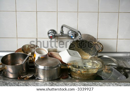 Pile of dirty dishes in the metal sink - stock photo