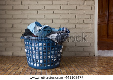 Pile of dirty laundry in a washing basket  - stock photo