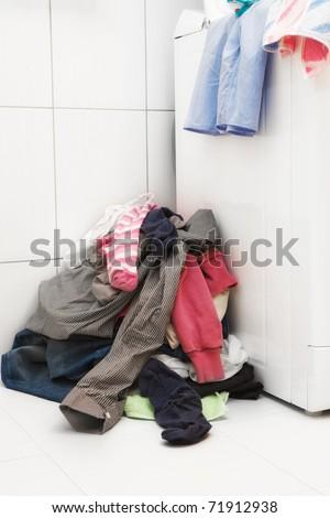 Pile of dirty laundry next to washing machine - stock photo