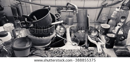 Pile of dirty utensils in a kitchen washbasin - stock photo