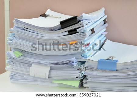 Pile of documents on desk at workplace. - stock photo