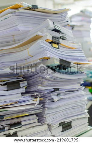 Pile of documents on desk stack up high waiting to be managed - stock photo