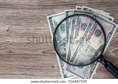 pile of dollar  banknotes under looking glass - stock photo