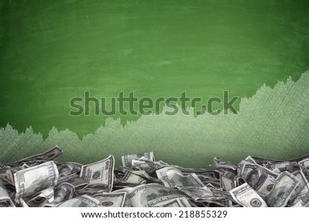 Pile of dollar bills on blackboard background - stock photo