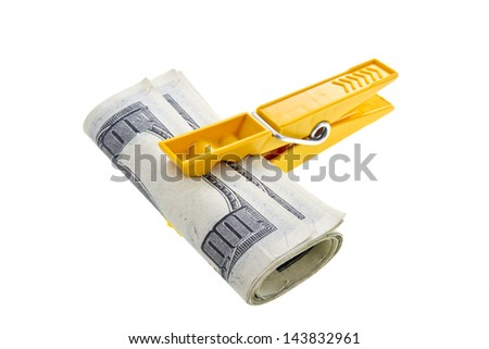 Pile of dollars with yellow clothespin isolated on white - stock photo