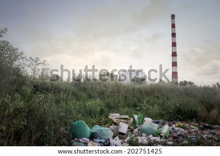 Pile of domestic garbage on wild dump from factory chimneys in the background - stock photo
