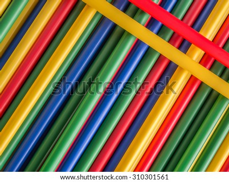 Pile of drinking straws in yellow, red, green and blue color
