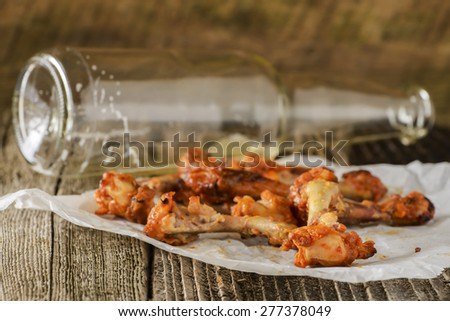 Pile of eaten barbecued chicken wings on a rustic wood background. - stock photo