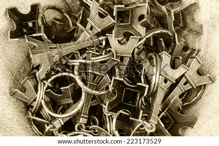Pile of Eiffel Tower trinkets in the wicker basket. Typical souvenir from Paris. Aged photo. Sepia. - stock photo