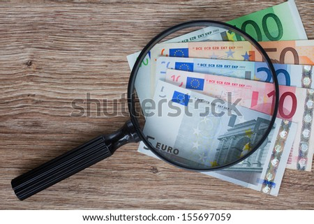 pile of euro banknotes under magnifying glass - stock photo