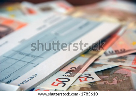 pile of euro bills under business cheque book