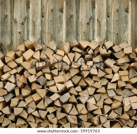 Pile of firewood against old wooden fence - stock photo
