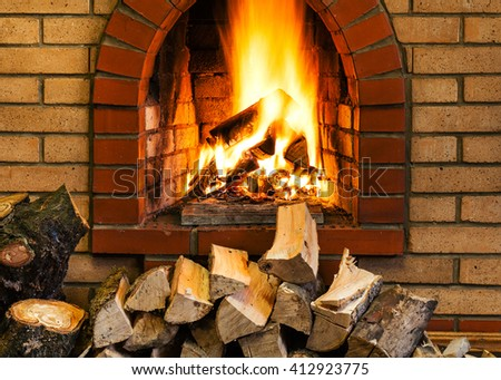 pile of firewood and fire in indoor brick fireplace in country cottage
