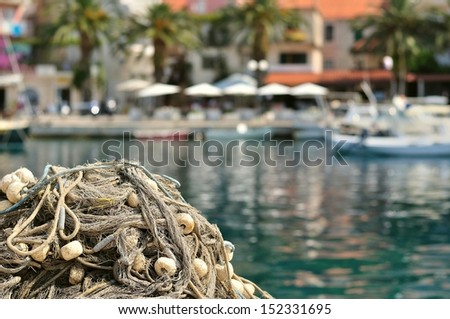 Pile of fishing nets with floats on a quay with blurred boats on background. Podgora, Croatia - stock photo