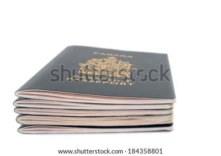 Pile of five passports viewed from the side on white background - stock photo
