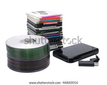 Pile of floppy disks, cd-roms, external hard drive and pen drive over white - stock photo