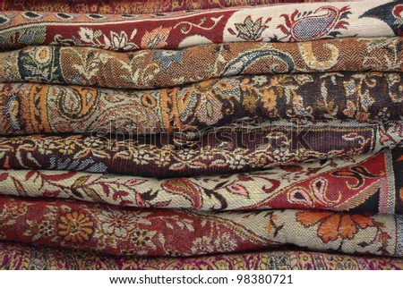 Pile of folded colour fabrics and shawls (scarfs) at the market - stock photo